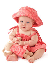 Smiling baby girl in pink dress and sun hat sits and plays with