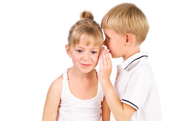 5-7 years old boy tells a secret to the girl isolated over white