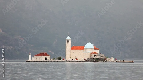 The old church on island in a sea on foggy mountains background