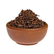Dry black tea in a clay cup