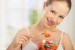 young healthy woman eats vegetable salad