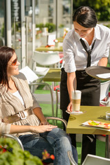 Waitress serve woman latte at cafe bar