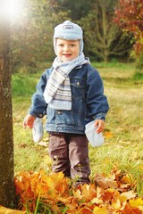 Boy within leaves in autumn