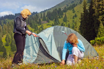 Two young women set the tent.