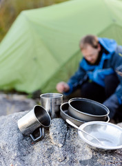 Outdoors man cooking with metal cookware utensils
