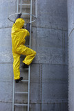 specialist in protective uniform going up a metal ladder poster