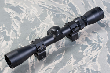rifle scope on camouflaged background