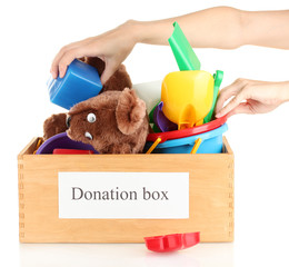Donation box with children toys on white background close-up