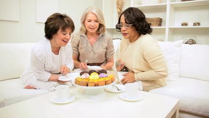 Multi Ethnic Retired Girlfriends Enjoying Tea Cupcakes