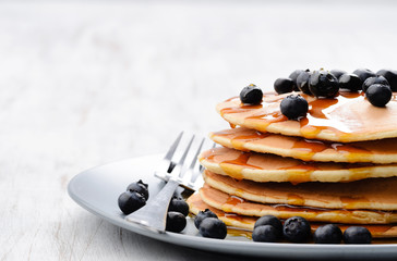 Pancake stack with maple syrup and blueberries