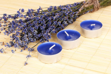 Lavender flowers with candles on bamboo mat