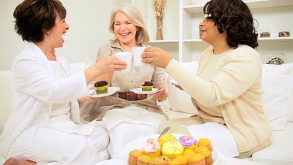 Multi Ethnic Senior Girlfriends Laughing Coffee Cupcakes