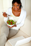 Adult woman eating healthy green salad poster