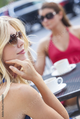 Two Young Women Friends Drinking Coffee in Cafe