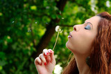 cute woman is blowing a blowball