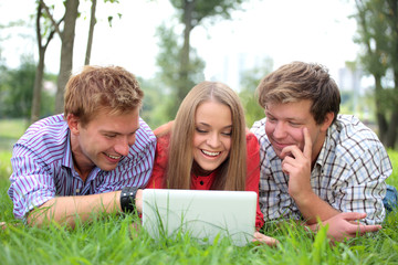 smiling students with laptop on natural background