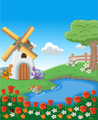 Green garden with beautiful spring flowers, lake and windmill