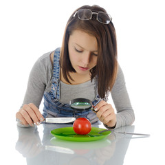 Girl investigating tomato.