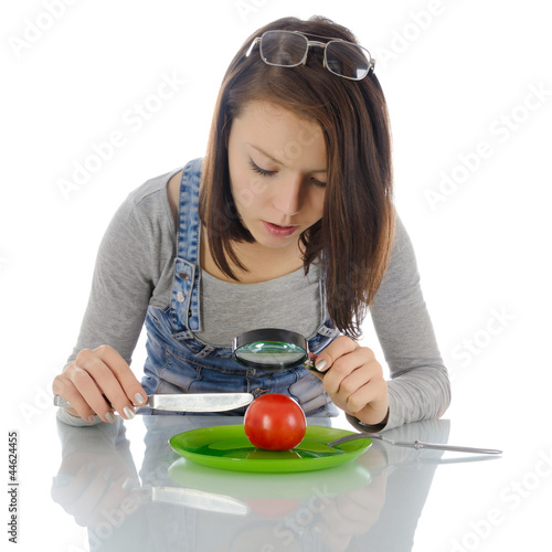Girl investigating tomato.