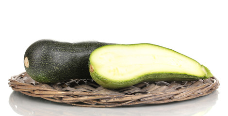 fresh zucchini and half on wicker mat isolated on white