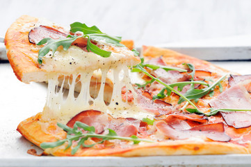 Gourmet rustic pizza lifted melted mozarella cheese