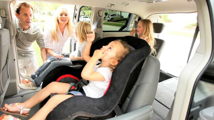Parents Putting Children Family Car Seats