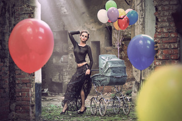 Young sexy woman with balloons and baby carriage
