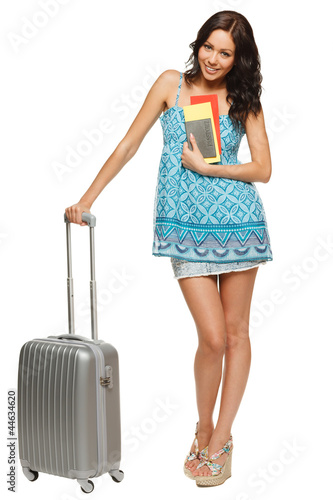 Full length of female standing with suitcase, passport, tickets