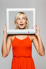 Surprised woman looking through TV computer screen, looking up