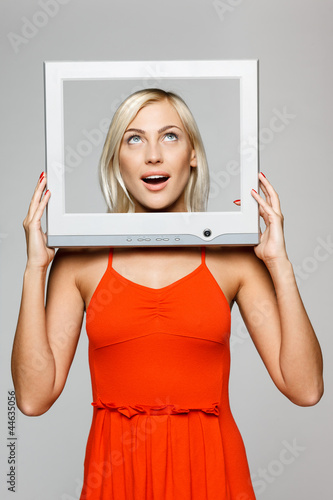 Surprised female looking through TV computer screen, looking up