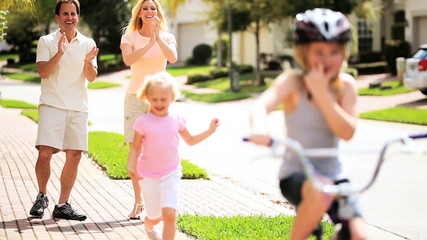 Young Parents Child Encouraging Sister on Bicycle