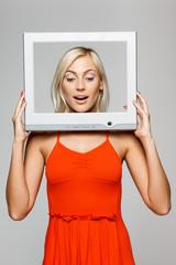 Surprised female looking through tv computer frame, looking down
