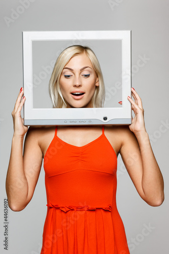 Surprised female looking through tv computer frame, looking down