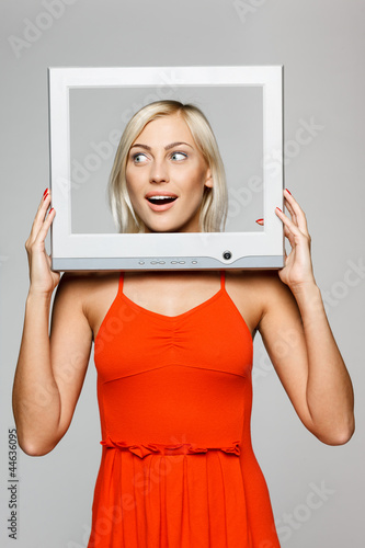 Surprised female looking through computer frame, looking to side