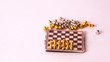 Small chessmen by turns fall from chessboard on white