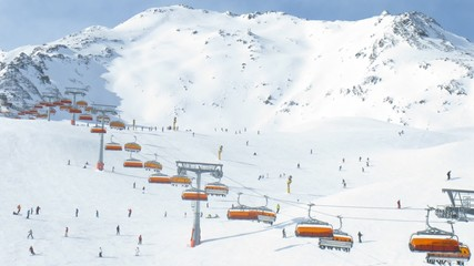 Rope-way with orange seats does descent and rise of skiers