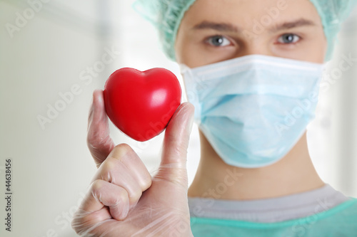 Male surgeon holding red heart