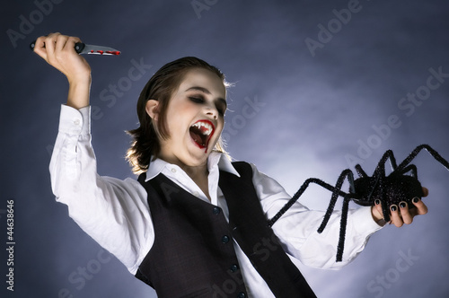 Mad vampire boy prepared to stab a spider