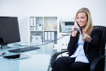 geschäftsfrau zeigt daumen hoch beim telefonieren