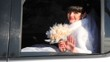 bride and with bouquet of roses waves hand from car