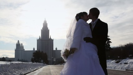 girl and man in wedding dresses kiss on area