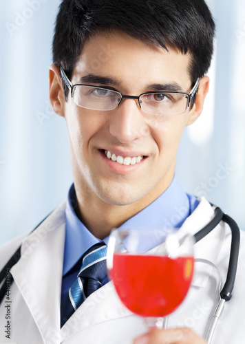 Smiling young doctor with redwine