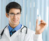 Happy doctor showing bottle of drugs