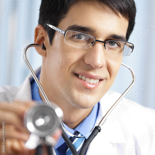 Happy doctor with stethoscope, at office