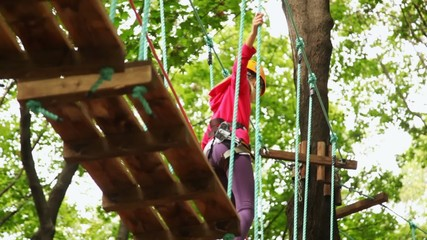 girl walks on suspended by cables on trees in wood to boards