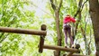 girl crosses on linked logs and suspended on height in wood