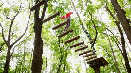 girl moves down downwards suspended on cable in wood
