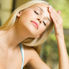 Young woman with headache or applying creme