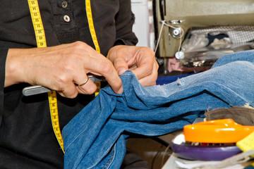 Schneiderin beim Ausbessern einer Jeanshose
