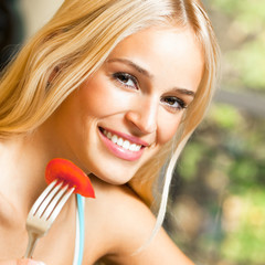 Happy smiling young woman eating salad